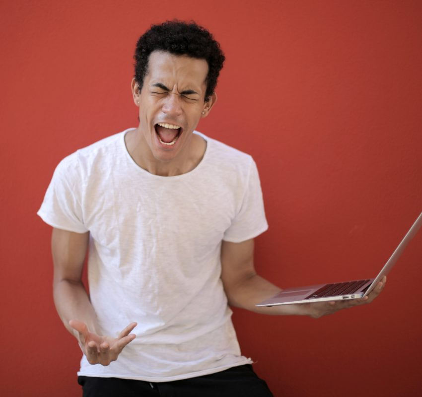 young-ethnic-male-with-laptop-screaming-3799830